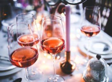 Ein dekorierter Tisch mit drei Weingläsern voller Rosé.