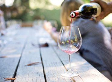 Eine Person schüttet eine Glas Rotwein an einem Holztisch ein.