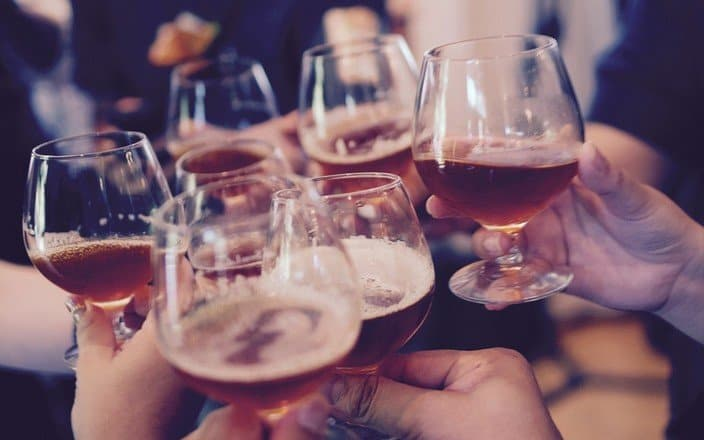 Personen stoßen mit einem Glas Wein miteinander an