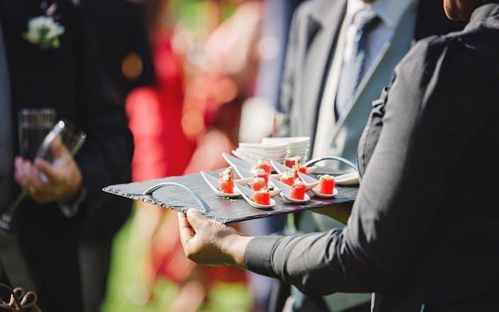 Servicekraft bietet Gast auf Firmenfeier ein Tablett mit Häppchen an
