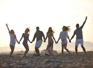 Gruppe junger Leute gemeinsam am Strand im Sonnenuntergang