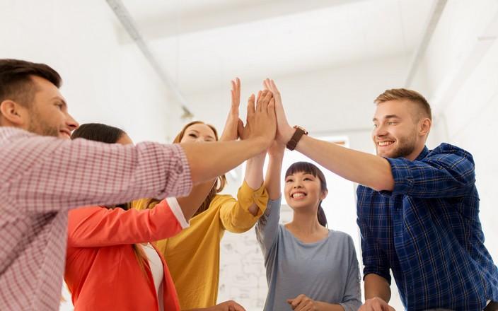Gut gelaunte Mitarbeiter schlagen ein auf ihren Erfolg als Team