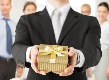 Geschäftsmann hält Weihnachtsgeschenk in Firma in die Kamera